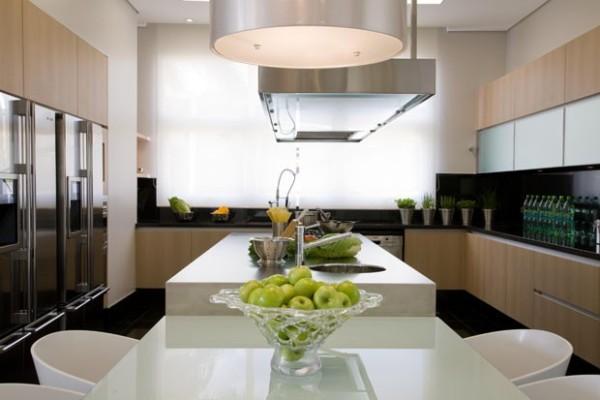 cozinha-grande-com-ilha-e-mesa-armarios-de-madeira-coifa-cooktop-600x400